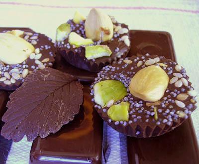 Ici, chocolats aux épices moulés dans des bacs à glaçons, chocolats noisette / pistache / graines de pavot et sésame moulés dans dans petits moules en papier et feuille en chocolat moulée sur feuille de fraisier.